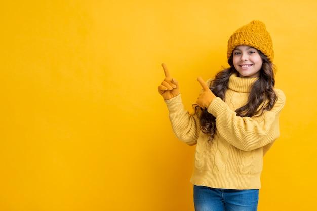 La ragazza si è vestita densamente su una priorità bassa gialla