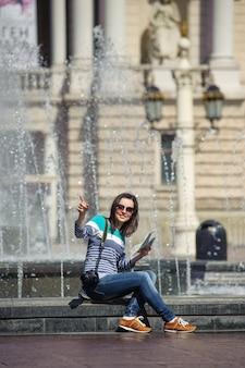 La ragazza si siede alla fontana con la mappa e la macchina fotografica che mostra il modo
