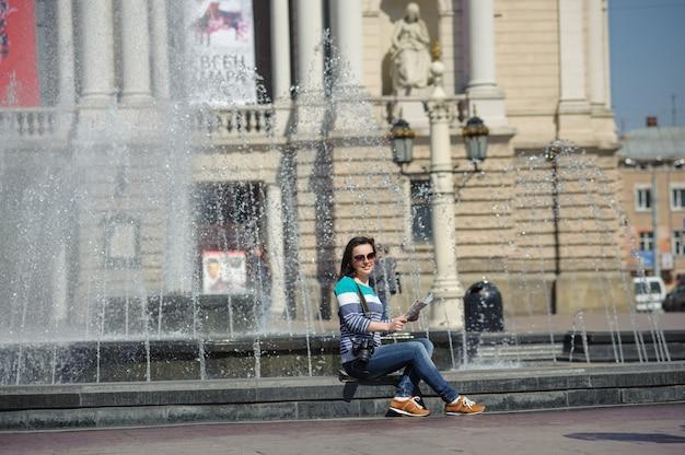 La ragazza si siede alla fontana con la mappa e la macchina fotografica
