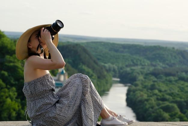 La ragazza si siede e scatta foto sullo sfondo della foresta e del fiume serpeggiante
