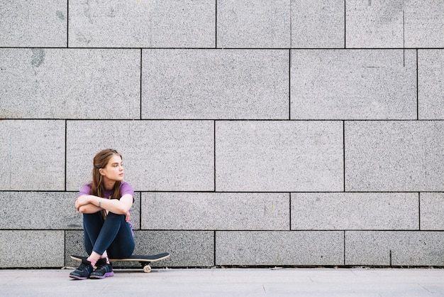 La ragazza si siede su un skateboard contro un muro di mattoni