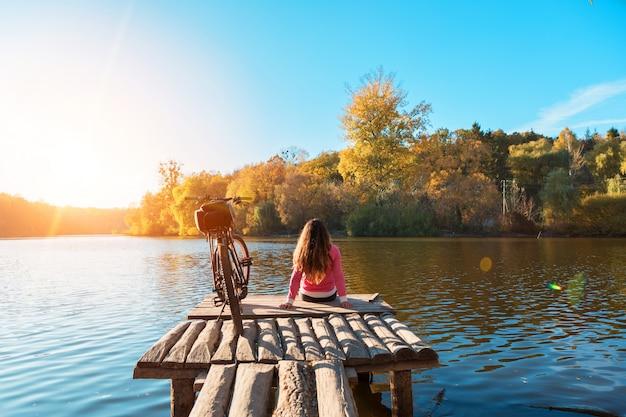 La ragazza si siede sulla riva del fiume. bici sul fiume con una borsa sul bagagliaio