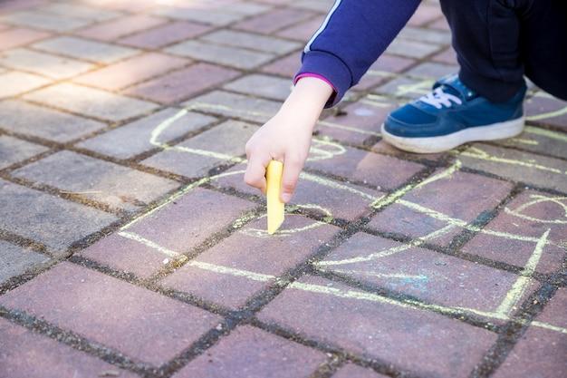 La ragazza si siede sulla strada asfaltata concreta., sulla via di pietra. bambini che dipingono linee, numeri con gesso su asfalto. messa a fuoco selettiva mani della bambina che dipingono sul marciapiede utilizzando un gesso colorato.