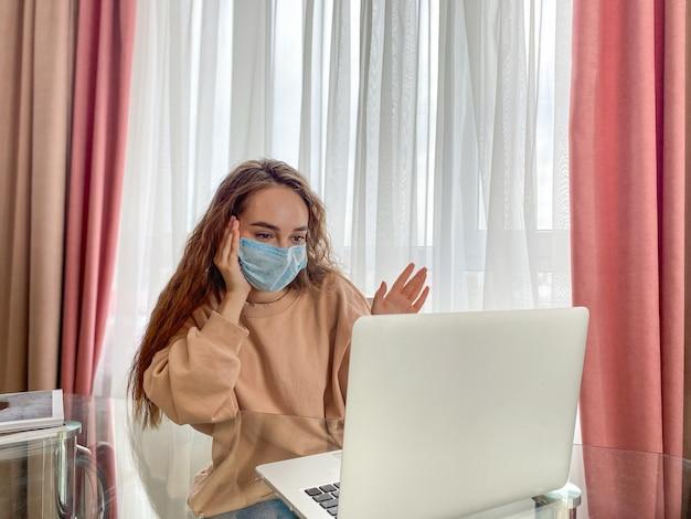 La ragazza si soffia il naso usando un tovagliolo di carta. la ragazza è seduta a casa per cure ambulatoriali. prevenzione dell'isolamento del coronavirus