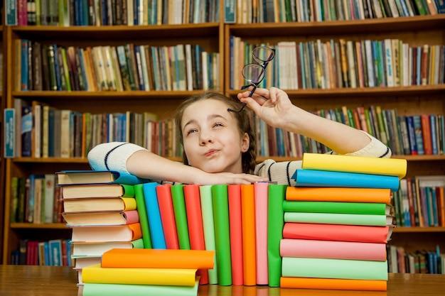 La ragazza sogna con i libri in biblioteca.