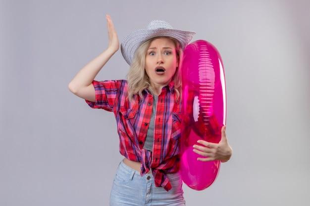 La ragazza sorpresa del viaggiatore che porta la camicia rossa in cappello che tiene l'anello gonfiabile ha sollevato la mano su fondo bianco isolato