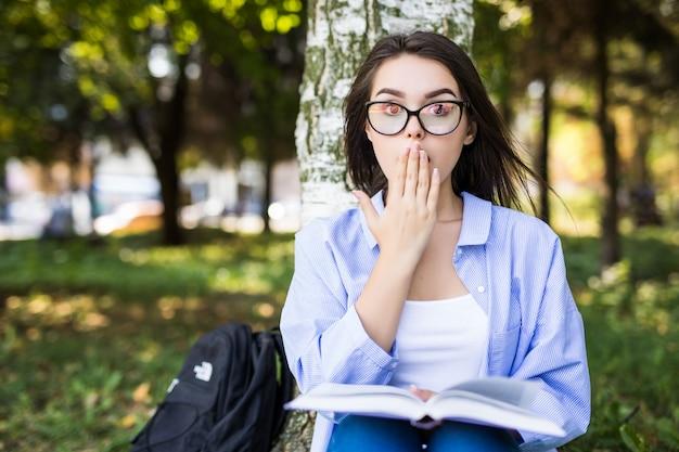 La ragazza sorpresa in giacca di jeans e occhiali legge il libro contro il parco verde estivo.