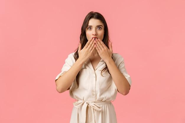 La ragazza sorpresa non si aspettava che l'amica la baciava, toccando il labbro e sembrando stupita dall'espressione meravigliata ed eccitata, indossando un vestito carino, reagendo stupita, in piedi muro rosa