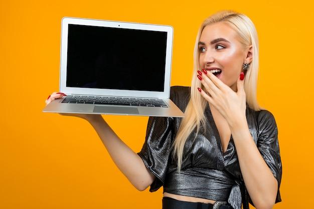 La ragazza sorpresa tiene il computer portatile con il modello per la pagina web sulla parete gialla