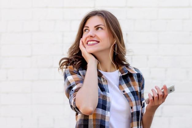 La ragazza sorride e ascolta la musica al telefono su uno sfondo di un muro di mattoni bianco