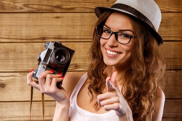 La ragazza sorride e fa una foto su una vecchia macchina fotografica.