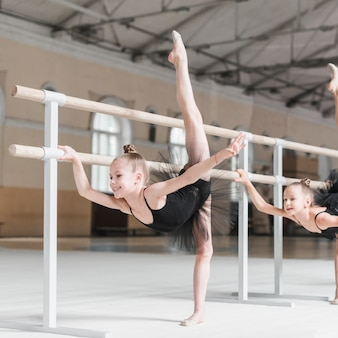 La ragazza sorridente che pratica il balletto balla con il supporto della sbarra nella classe di ballo