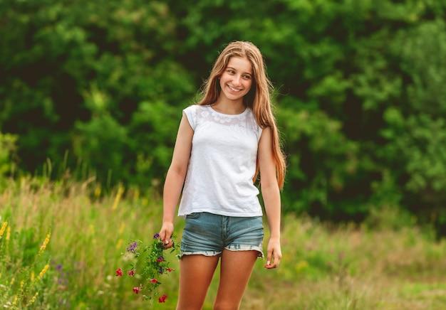 La ragazza sorridente con il campo fiorisce il mazzo