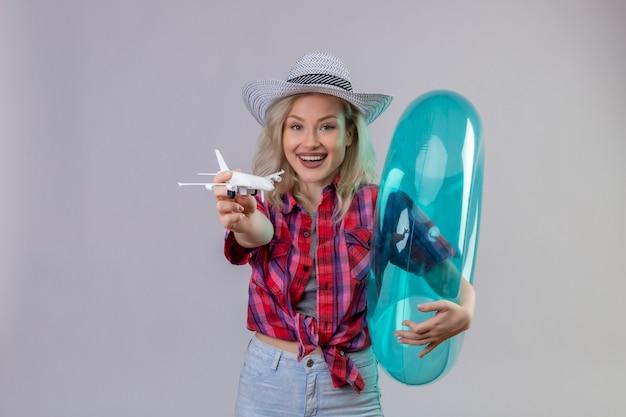 La ragazza sorridente del viaggiatore che porta la camicia rossa in cappello che tiene l'anello gonfiabile ha tenuto fuori al piano del giocattolo della macchina fotografica su fondo bianco isolato