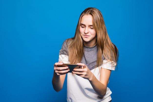 La ragazza sorridente felice con il telefono cellulare legge il messaggio davanti a fondo blu