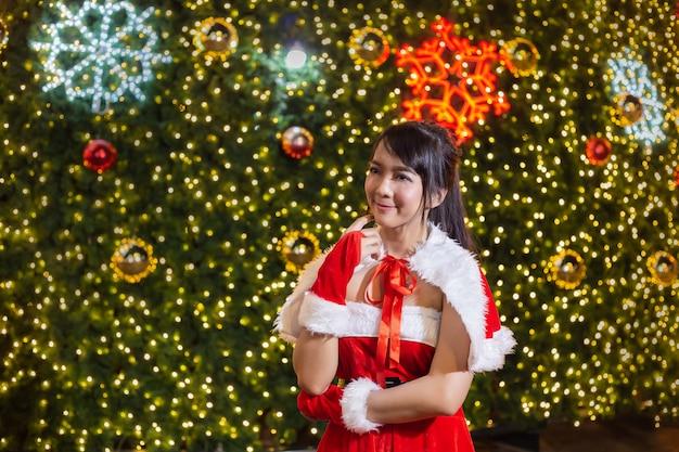 La ragazza sorridente felice della santa è sveglia in vestito rosso con la priorità bassa dell'albero di natale