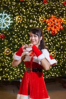 La ragazza sorridente felice della santa è sveglia nel cuore rosso di amore della mano e del vestito con l'albero di natale