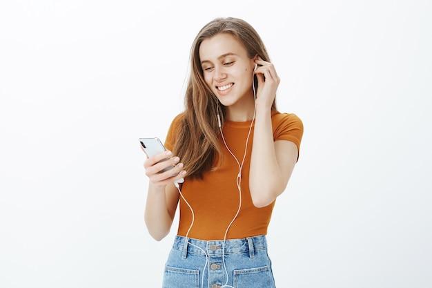 La ragazza sorridente felice ha messo le cuffie, ascolta il podcast o la musica sul telefono cellulare