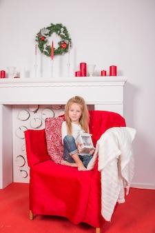 La ragazza sorridente graziosa che tiene la lanterna di festa, casa è decorata prima della festa di natale decorazione di buon natale in salone anno nuovo. immagine verticale