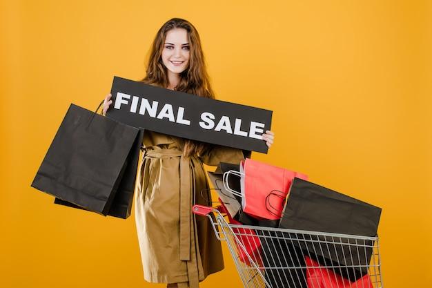 La ragazza sorridente ha il segno finale di vendita con il carrello pieno di sacchetti della spesa isolati sopra giallo