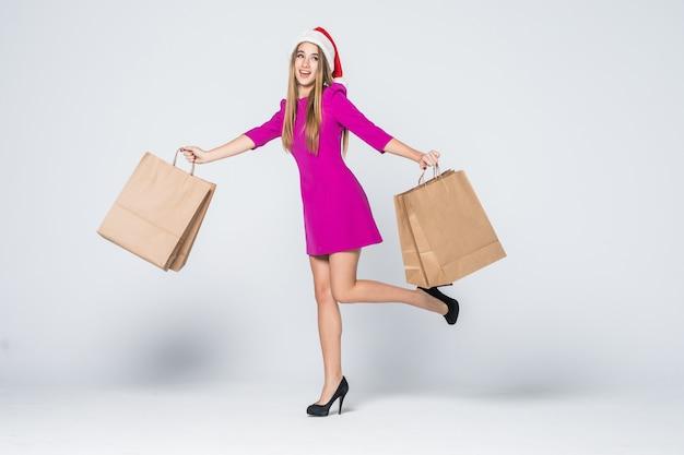 La ragazza sorridente in breve vestito rosa e cappello del nuovo anno dei talloni tiene i sacchetti di carta isolati su fondo bianco