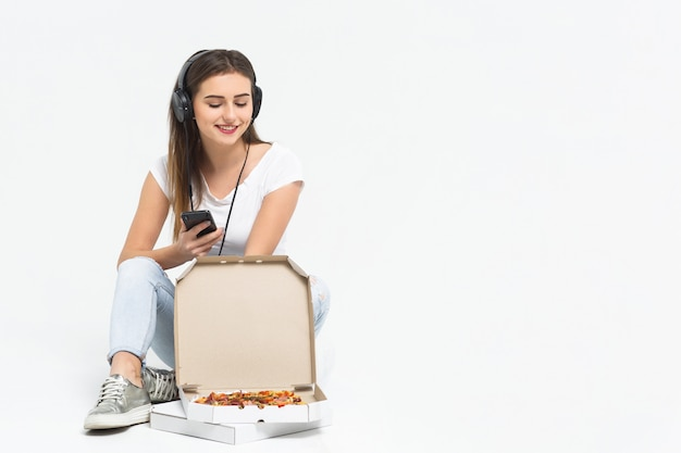 La ragazza sorridente si diverte con la pizza, è seduta sul pavimento e ascolta la musica in cuffia.