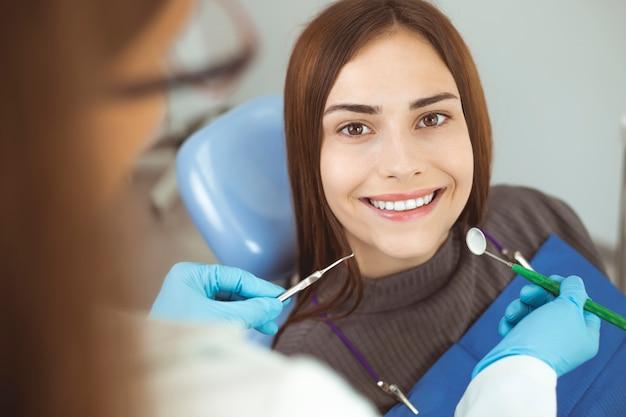 La ragazza sorridente tratta i denti mentre si siede nella sedia dentaria al medico.
