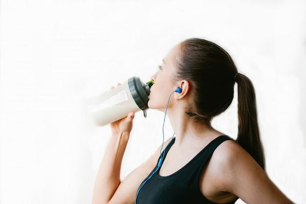 La ragazza sportiva beve da uno shaker