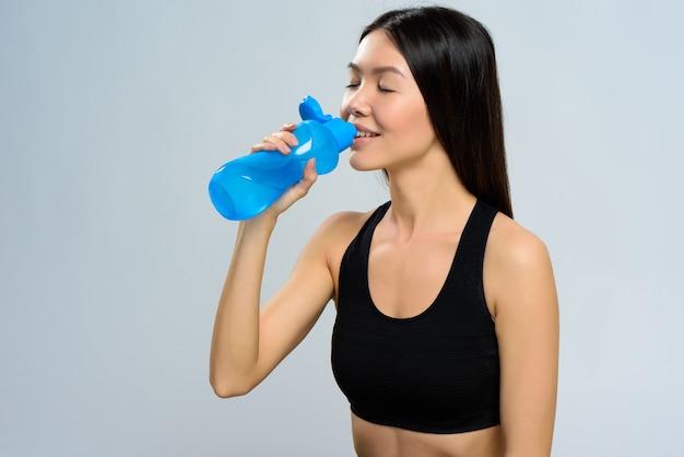 La ragazza sportiva beve l'acqua da una bottiglia blu.