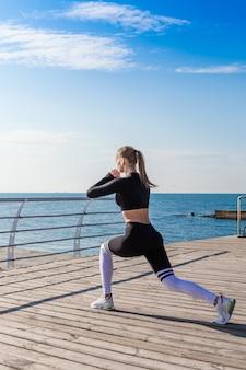 La ragazza sportiva che fa gli edifici occupati si avvicina al mare