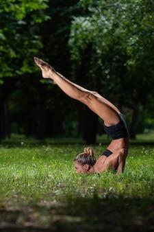 La ragazza sportiva dell'acrobata che sta sulle sue mani, esegue un elemento acrobatico