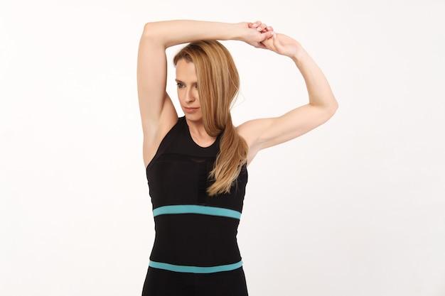 La ragazza sportiva fa esercizi di stretching