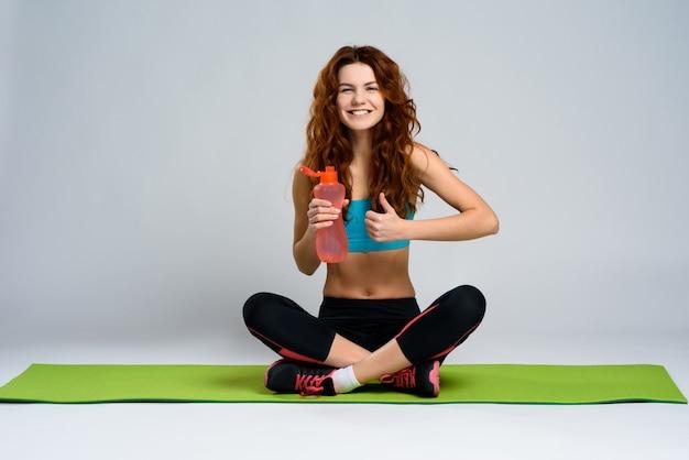 La ragazza sportiva sta sorridendo e mostra il gesto ok.