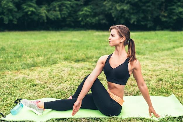 La ragazza sportiva sveglia che mostra l'allungamento si esercita all'aperto