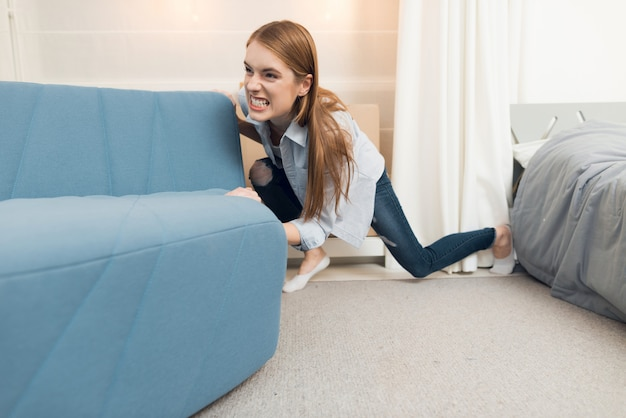La ragazza sposta il divano mentre si trasferisce in una nuova casa.