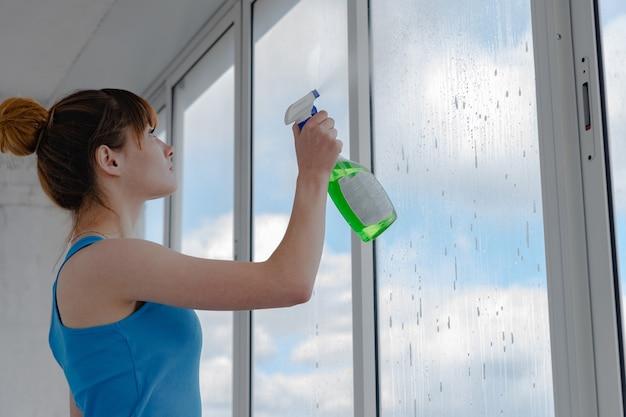 La ragazza spruzza un liquido per lavare le finestre su un vetro sporco. una donna in una maglietta blu lava una finestra.