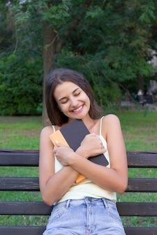 La ragazza sta abbracciando il suo manuale favorito nel parco