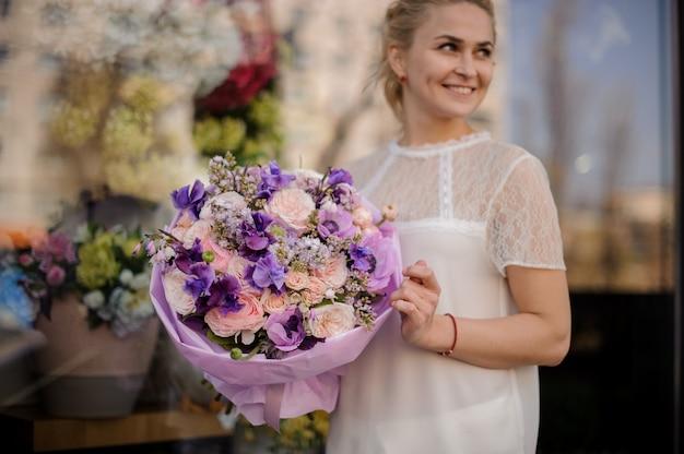 La ragazza sta all'aperto con un bouquet di fiori sorprendente