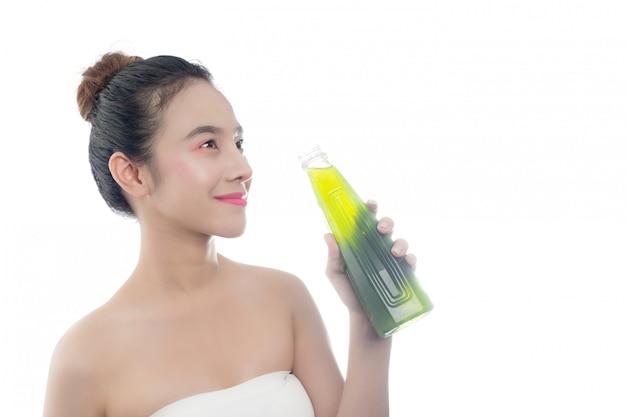 La ragazza sta bevendo acqua verde su uno sfondo bianco.