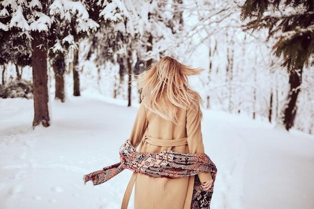La ragazza sta camminando in un parco d'inverno