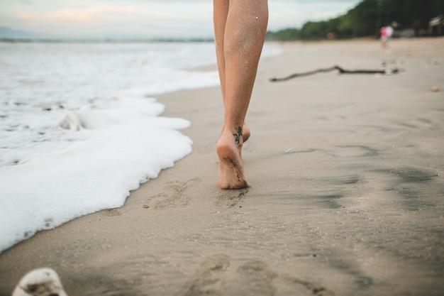 La ragazza sta camminando lungo la spiaggia