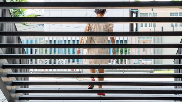 La ragazza sta camminando sulla scala d'acciaio esterna con la città del paesaggio.