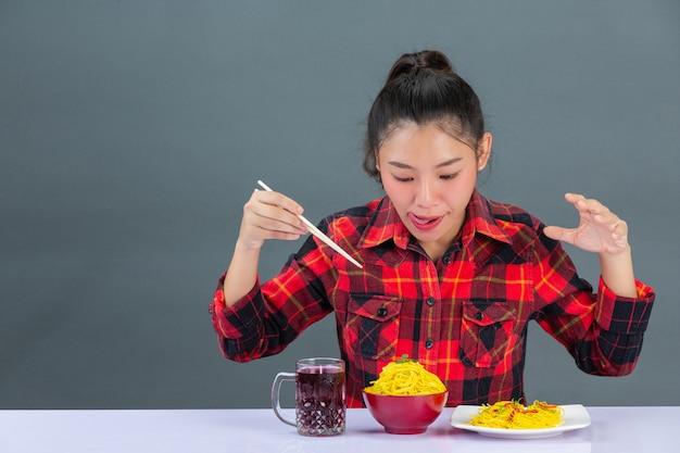 La ragazza sta godendo mangiando gli spaghetti a casa