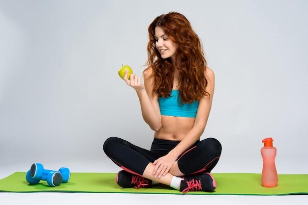 La ragazza sta guardando sulla mela verde e sorridente.