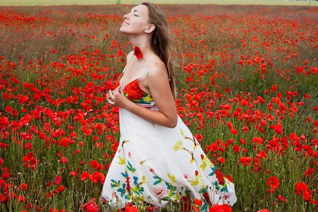 La ragazza sta in un campo di papaveri
