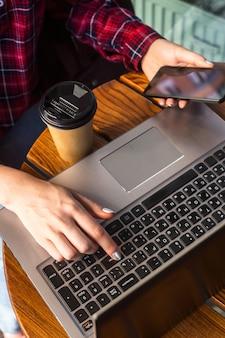 La ragazza sta lavorando dietro un computer portatile a un tavolo in un caffè accanto a una tazza di caffè