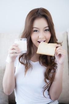 La ragazza sta mangiando il pane tostato fresco che tiene un bicchiere di latte