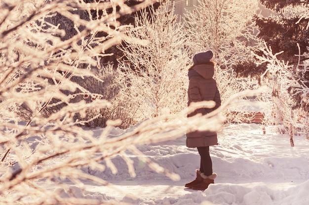 La ragazza sta nel parco dell'inverno.