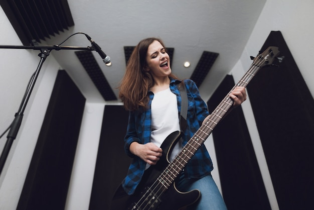 La ragazza sta registrando una canzone in un moderno studio di registrazione.