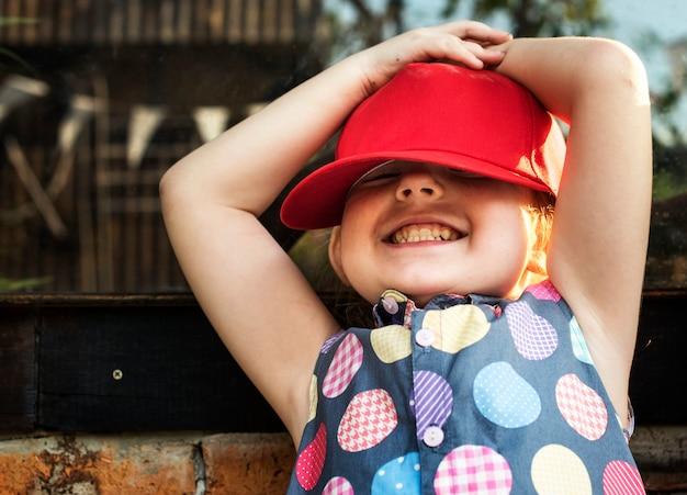 La ragazza sta sorridendo con il berretto rosso